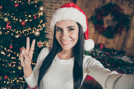 Enjoy christmas atmosphere. Close up photo of positive cheerful girl in santa claus hat blogging on x-mas time take selfie make v-sign in room house with newyear wreath garlands decoration indoors Banque d'images - 132552601