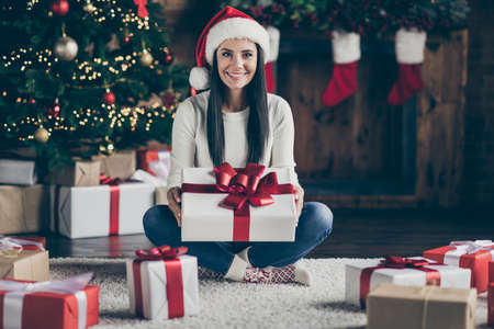 Full length photo of positive girl wear santa claus hat hold big giftbox get on christmas night enjoy newyear tradition sit on floor carpet in house with festive x-mas illumination indoors