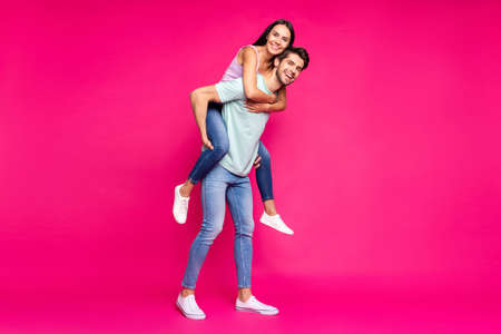 Full length photo of funny guy and lady holding piggyback spending, best free time wear casual clothes isolated vibrant vivid pink color background