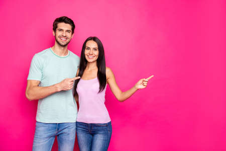 Photo of funny couple guy and lady indicating fingers to empty space, advising black friday shopping wear casual clothes isolated vivid pink color background Standard-Bild