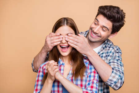 Photo of cheerful cute nice gorgeous fascinating couple with him covering her eyes and her ecstatic and within temptation of upcoming, surprise isolated over beige pastel color background 版權商用圖片