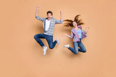 Full length photo of two people crazy lady guy jumping high overjoyed mood celebrate, vacation summer beginning wear casual clothes isolated beige color background Фото со стока
