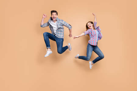 Full length photo of two people crazy lady guy jumping high overjoyed, mood celebrate sale shopping prices black friday wear casual clothes isolated beige color background