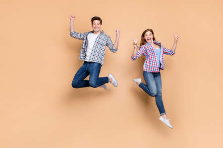 Full length photo of two people crazy lady guy jumping high showing, v-sign symbol celebrating successful win wear casual plaid jeans clothes isolated beige color background