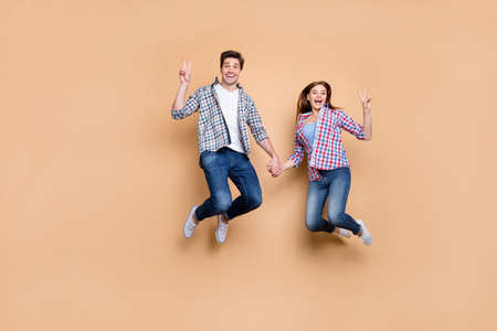 Hi there. Full length photo of two people lady guy jumping high holding, hands showing v-sign symbols wear casual plaid jeans clothes isolated beige color background