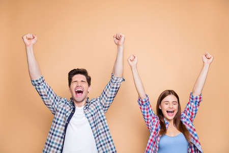 Portrait of his he her she nice attractive satisfied delighted cheerful cheery, couple wearing checked shirt celebrating rising hands up good luck isolated over beige pastel color background