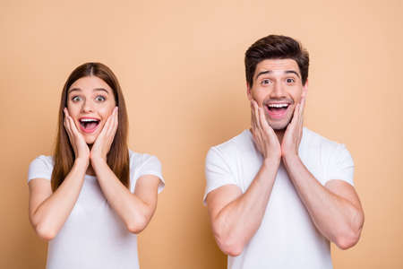 Close-up portrait of his he her she nice attractive ecstatic cheerful cheery overjoyed couple wearing white t-shirt great news delight reaction isolated over beige pastel color background