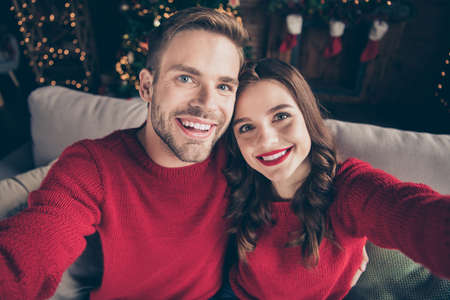 Photo of charming couple spending christmas together making selfies in decorated garland lights room near newyear tree indoors wear red pullovers Banque d'images - 132554583