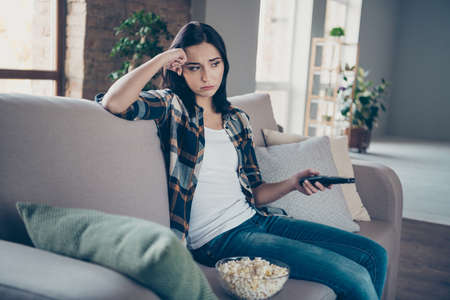 Photo of pretty lady holding remote controller and popcorn plate upset of favorite serial ending sitting sofa wearing casual clothes apartment indoors Imagens