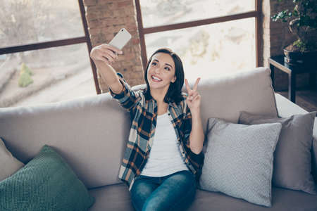 Photo of charming lady holding telephone making selfies for blog showing v-sign symbol sitting comfortable sofa wearing casual plaid shirt and jeans apartment indoors