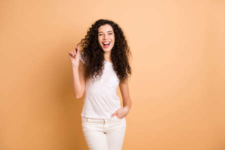 Photo of pretty funny lady showing perfect condition wavy curls after visiting amazing salon stylist wear white casual clothes isolated beige pastel color background