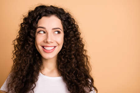 Close up photo of cheerful charming cute nice girl looking into empty space nearby smiling toothily isolated over pasel beige color background
