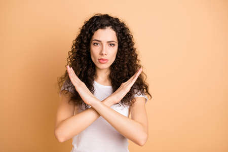 Photo of trendy serious brunette casual confident girlfriend showing you hands crossed restricting your access isolated over beige pastel color background