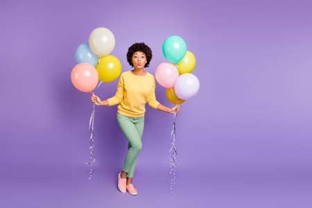 Full body photo of dreamy afro american girl date boyfriend on 14-february holidays get hold baloons send air kisses wear yellow jumper green pants trousers isolated violet purple color background