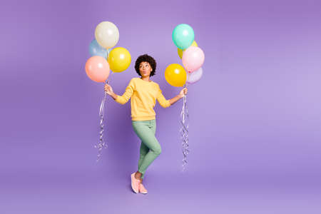 Full length photo of lovely brown hair afro american girl celebrate 14-february event hold many baloons send air kiss enjoy fall autumn time wear casual style clothing isolated purple color background