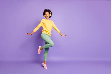 Full length body size turned photo of cheerful positive cute nice charming girlfriend dancing in headphones wearing yellow sweater green pants trousers isolated over violet pastel color background Stockfoto
