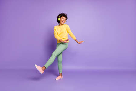 Full length body size photo of cheerful wavy curly haired sweet pretty girl of freedom wearing green pants trousers dancing listening to her music out of headphones isolated over violet color pastel background