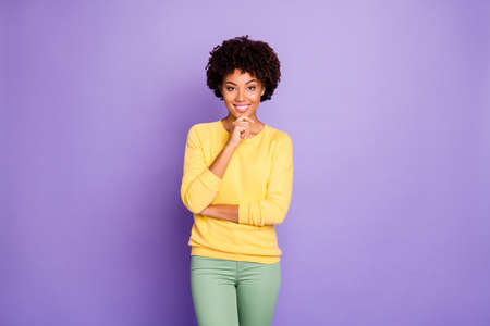 Photo of cheerful puzzled cute girl wearing yellow clothing posing in front of camera touching her chin smiling toothily beaming isolated over purple pastel color background