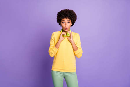 Photo of curly wavy trendy girlfriend shocked finding her favorite song and hearing from headphones she holds with hands wearing yellow sweater pants trousers isolated purple pastel color background