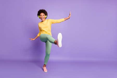 Foto de cuerpo entero de la novia ondulada, alegre, emocionada, extasiada y llena de alegría, gritando, bailando, escuchando música, fingiendo estar pateando con la pierna cerca del espacio vacío aislado sobre fondo de color violeta pastel