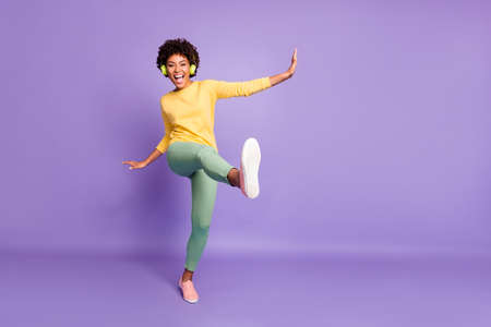 Ganzkörperfoto in voller Länge von wellenförmiger, fröhlicher, aufgeregter, überglücklicher, schreiender Freundin, die Musik hört, die vorgibt, mit dem Bein in der Nähe des leeren Raums zu treten, einzeln auf violettem Pastellhintergrund