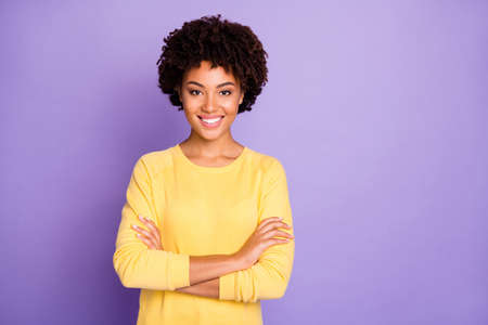 Photo of trendy sweet pretty attractive young representative of business people community standing confidently with arms crossed smiling toothily wearing yellow sweater isolated over purple pastel color background