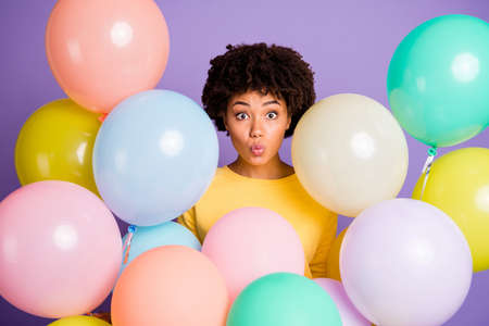 Close-up portrait of her she nice attractive lovely lovable girlish funky funny cheerful wavy-haired girl sending kiss among air balls isolated over violet purple lilac pastel color background