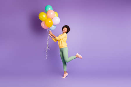 Full length photo of positive afro american girl hold baloon present for woman day feel content have autumn holiday walk with boyfriend wear stylish outfit isolated violet purple color background