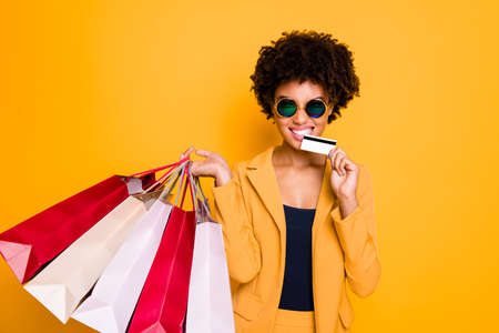 I want buy all. Portrait of crazy brunette curly hair lady go shopping in center hold bags bite plastic card spend money pay purchases wear autumn style suit isolated yellow color background Stok Fotoğraf