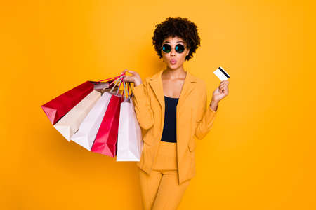 Portrait of funky funny brunette wavy hair lady went shopping for bargain in center hold bags pay debit card on autumn holidays wear style pants trousers suit isolated yellow color background Stock fotó