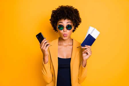 Portrait of amazed brunette curly hair afro american girl tourist hold cellphone passport want go summer journey abroad voyage try reserve hotel wear style suit blazer isolated over yellow color background