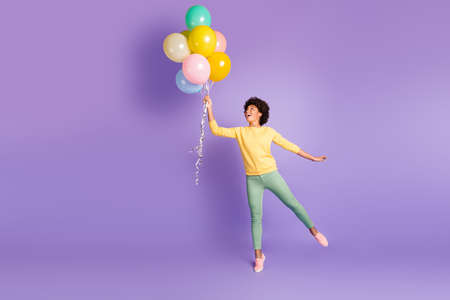 Full length profile side photo of amazed funky funny dark skin girl hold many, baloons think she can fly in the sky enjoy rejoice wear trendy green sweater outfit isolated over violet color background