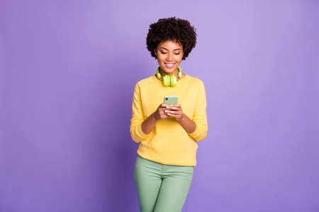 Photo of wavy trendy stylish cheerful girlfriend wearing yellow sweater green pants trousers browsing through her telephone with earphones around her neck isolated over pastel color violet background