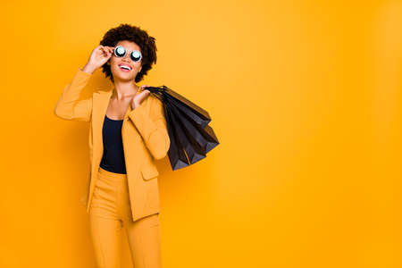 Portrait of positive cheerful lady have fun on leisure time touch specs enjoy 50 off sales bargain feel content she shopped wear style clothes pants trousers isolated yellow color background