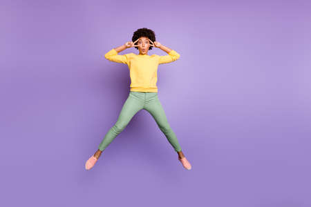 Full size photo of funky funny brunette curly hair mulatto girl jump make v-signs near her face wear casual style clothing sneakers isolated violet color background