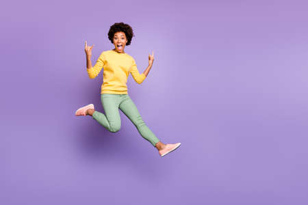 Lets rock. Full size photo of cheerful crazy mulatto girl fool on autumn spring holiday show horns true rocker sign wear yellow pullover green pants trousers isolated purple violet color background