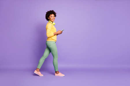 Full length body size photo of side profile walking smiling toothy girl going side profile holding telephone wearing yellow sweater green pants trousers isolated over violet pastel color background