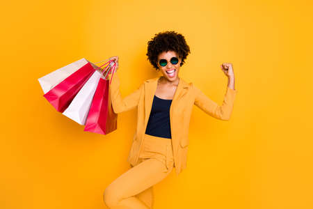 Portrait of delighted crazy brunette wavy hair dark skin lady go shopping lucky find black friday sales raise fists scream yes buy hold bags wear fashion style pants isolated yellow color background