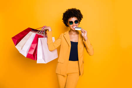 Portrait of crazy brunette curly hair dark skin girl mall client in sunglass find discounts go shopping buy bite debit card easy payment wear style pants trousers isolated yellow color background Banco de Imagens
