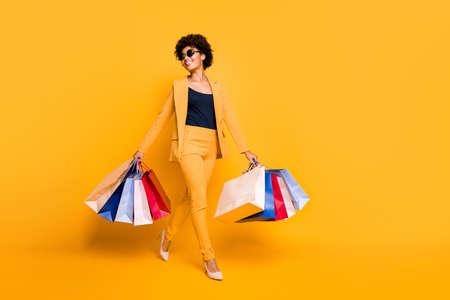 Foto in voller Größe von positiv fröhlichen Mädchen, die sich in der Freizeit träumen, verträumt halten Taschen vom Einkaufszentrum tragen Stilettos im Stil von Blazer-Hosen einzeln auf gelbem Hintergrund
