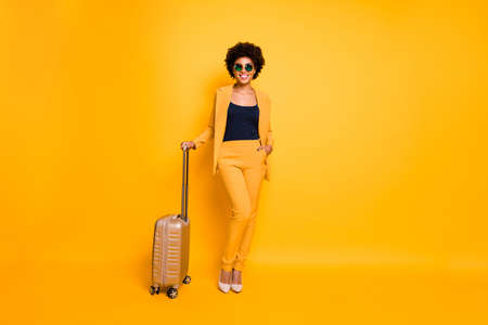 Full length photo of charming chic stunning dark skin girl feel positive ready go abroad for trip wear fashionable outfit trousers shoes isolated over yellow color background Stockfoto