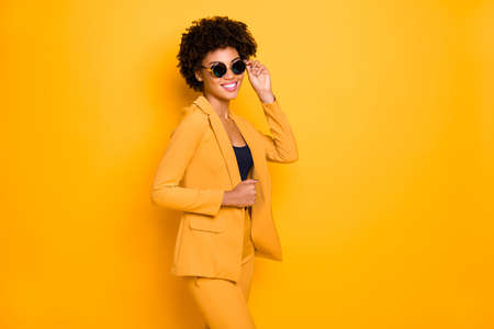 Portrait of gorgeous elegant businesswoman dark skin lady feel confident cool touch her spectacles enjoy her beauty vogue wear stylish clothes isolated over yellow color background
