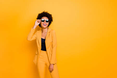 Portrait of her she nice fashionable attractive luxurious cheerful cheery wavy-haired girl touching specs isolated over bright vivid shine vibrant yellow color background