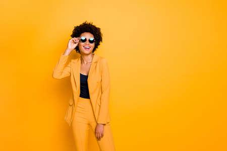 Portret van haar mooie modieuze aantrekkelijke luxe vrolijke vrolijke golvende haren meisje aanraken van specificaties geïsoleerd over heldere levendige glans levendige gele kleur achtergrond