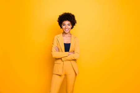 Portrait of her she nice-looking attractive lovely content cheerful cheery wavy-haired girl folded arms spring clothing trend isolated over bright vivid shine vibrant yellow color background