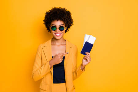 Portrait of positive cheerful brunette hair girl in sunglass hold passport point index finger recommend perfect summer tour voyage wear style blazer suit isolated over yellow color background