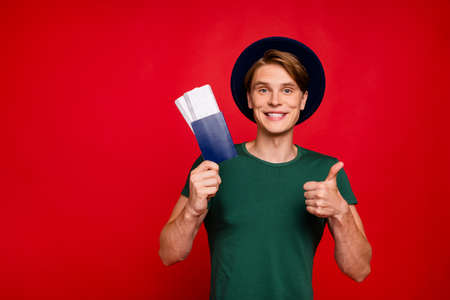 Portrait of positive brunette hair guy traveler tourist hold passport tickets show thumb up sign recommend good tour walk abroad wear blue velvet hat green t-shirt isolated over red color background
