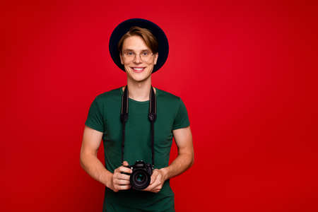 Portrait of positive cheerful guy have hobby on spring voyage hold his digital dlsr camera wear casual good look clothes isolated over red color background