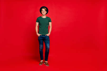 Full body photo of charming guy in blue hat real modest rich wealthy millionaire put hands in pockets feel glad ion summer vacations wear green t-shirt good look outfit isolated red color background Imagens