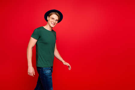 Turned photo of modest stunning charming millionaire guy go walk on summer holidays wear blue headwear green t-shirt denim jeans isolated over red color background